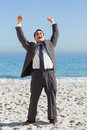 Victorious businessman in suit holding arms up on the beach Royalty Free Stock Photo