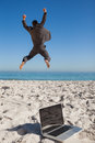 Victorious businessman in suit jumping leaving his laptop on the beach Stock Image