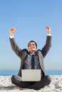 Victorious young businessman with his laptop on the beach Royalty Free Stock Photography