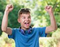 Victory screaming boy teen year old winner with headphones and sunglasses posing outdoors Royalty Free Stock Photo