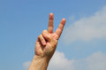 Victory sign with two fingers a finger a blue sky background Royalty Free Stock Images