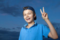 Victory teenage boy standing outside its evening he is giving the sign Royalty Free Stock Photo