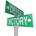 Victory vs defeat two way street road signs win or lose the words and on to illustrate the choice between winning losing a game Royalty Free Stock Photo