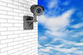 Video camera security system over brick wall with a sky background Stock Images