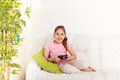 Video games for girls happy caucasian girl playing holding game controller sitting on the coach in living room Stock Photos