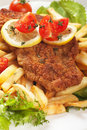 Viener schnitzel breaded steak with french fries lettuce and tomato Royalty Free Stock Images