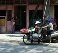 Vietnam - Hanoi - Typical street scene -ladies chatting in doorway whilst man on motorcycle and lady on pushbike go past Royalty Free Stock Photo