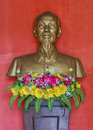 Vietnam quang binh province bust of ho chi minh bronze against red with pink and yellow plastic flowers in green Stock Image