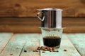 Vietnamese black coffee brewed in French drip filter on turquoise wooden table Royalty Free Stock Photo