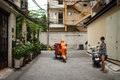 Vietnamese sanitation worker ho chi minh city vietnam – june garbage man pushing garbage cart in an alley in district with woman Stock Images