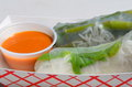 Vietnamese summer rolls goi cuon with traditional peanut dipping sauce served by a street vendor in a paper dish they are Stock Photography