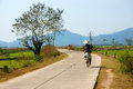 Vietnamese woman riding bicycle buon me thuot viet nam feb on country road beautiful of natural landscape at daklak countryside Stock Photography