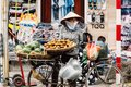 Vietnamese woman wearing asian conical hat sell fruits on her bicycle at street of Hanoi, Vietnam