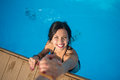 View from above of girl in the swimming pool holding a man`s hand trying to get out at sunny day Royalty Free Stock Photo