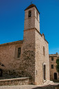 View alley and church with stone steeple tower in Saint-Paul-de-Vence. Royalty Free Stock Photo