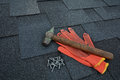 View on Asphalt Roofing Shingles Background. Roof Shingles - Roofing. Asphalt Roofing Shingles Hammer, Gloves and Nails Royalty Free Stock Photo