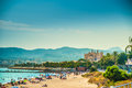 View of the beach of palma de mallorca with people lying on sand and gorgeous cathedral building visible in background Royalty Free Stock Photos