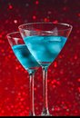 View from below of glasses of fresh blue cocktail with ice on red tint light bokeh background on bar table Royalty Free Stock Images