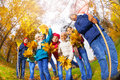 View from below of kids diversity in autumn park happy with rake and bunch yellow maple leaves standing close row the during Stock Images