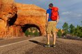 View from below of man on road near red canyon standing the during sunny summer day in usa Stock Photo