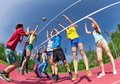View from below of teens playing volleyball on the game court together outside during summer sunny day Stock Images