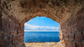 View of blue sea seascape from hole window frame in old stone wall and sky stonewall casing travel tourism Stock Image