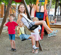 View on children swinging together on children`s playground Royalty Free Stock Photo