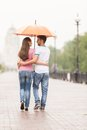 View of couple back under umbrella walking man huging women and looking at her in park Royalty Free Stock Photo