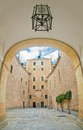 View of courtyard of  medieval castle from arc with lantern Royalty Free Stock Photo