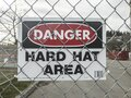 View of a Danger - Hard Hat Area sign on a chain link fence outside a construction zone Royalty Free Stock Photo