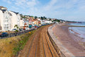 View of dawlish devon england with beach railway track and sea on blue sky summer day Stock Image