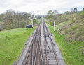 View down railway track in english countryside rural with overcast sky Royalty Free Stock Photography