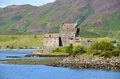 A view of eilean donan castle at dornie scotland with purple heather covering the hills in the background Stock Images