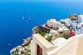 View of fira town santorini island crete greece white concrete staircases leading down to beautiful bay with clear blue sky and Stock Photos