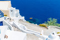 View of fira town santorini island crete greece white concrete staircases leading down to beautiful bay with clear blue sky and Royalty Free Stock Images