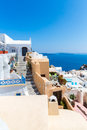 View of fira town santorini island crete greece white concrete staircases leading down to beautiful bay with clear blue sky and Stock Images