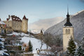 View of the gruyere castle the church and mountains in winter switzerland Stock Photos