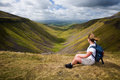 View from high cup nick on a windy day a walker sits enjoying the a cumbrian beauty spot called in england uk Royalty Free Stock Images