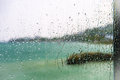 View of the lake through a window with wet glass Royalty Free Stock Photo