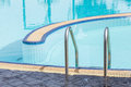 View of a light clear blue swimming pool with steel ladder. Royalty Free Stock Photo