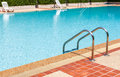 A view of a light clear blue swimming pool with steel ladder Royalty Free Stock Photo