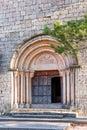 View of the main entrance to the church of Santa Maria de Siurana, in Siurana, Tarragona, Spain. Copy space for text. Vertical. Royalty Free Stock Photo
