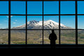 View of mount st helens woman standing in silhouette in front a picture window at national monument Royalty Free Stock Image