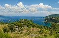 View of mountainous coast on sunny day against blue sky trees and plants covered hill with aegean sea at background amos bay Stock Images