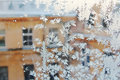 View of the old city house from a frozen winter window. Texture ice patterns on glass. Selective focus Royalty Free Stock Photo