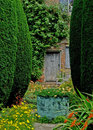 A view of an old country garden with copper vase and summer flowers Royalty Free Stock Photography