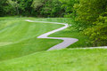 View of park nature and winding trail with people playing in background Royalty Free Stock Photo