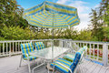 View of patio table set with umbrella in green and blue colors. Royalty Free Stock Photo