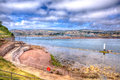 View from shaldon to teignmouth devon uk in hdr england with rocks and clear sea Royalty Free Stock Photography