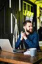View from the side bearded man in a shirt using a laptop sitting at a table in a cafe on the table cup of coffee Royalty Free Stock Photo